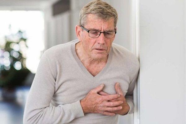 Пожилой мужчина держится за область сердца