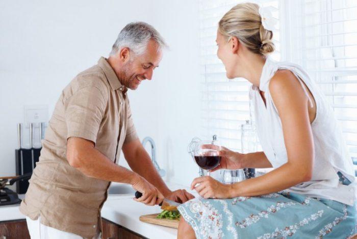 Мужчина на кухне режет зелень, женщина пьёт вино и что-то ему говорит, оба улыбаются