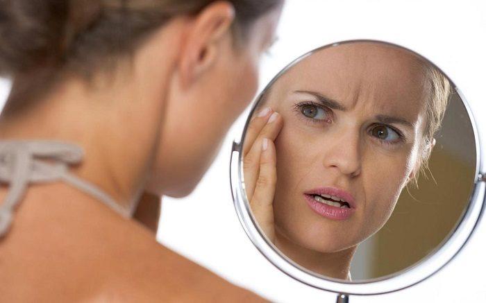 Женщина критически разглядывает себя в зеркало