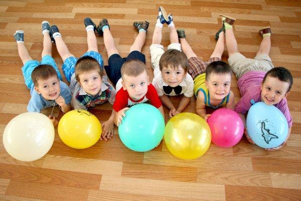 Мальчики лежат на полу с воздушными шариками