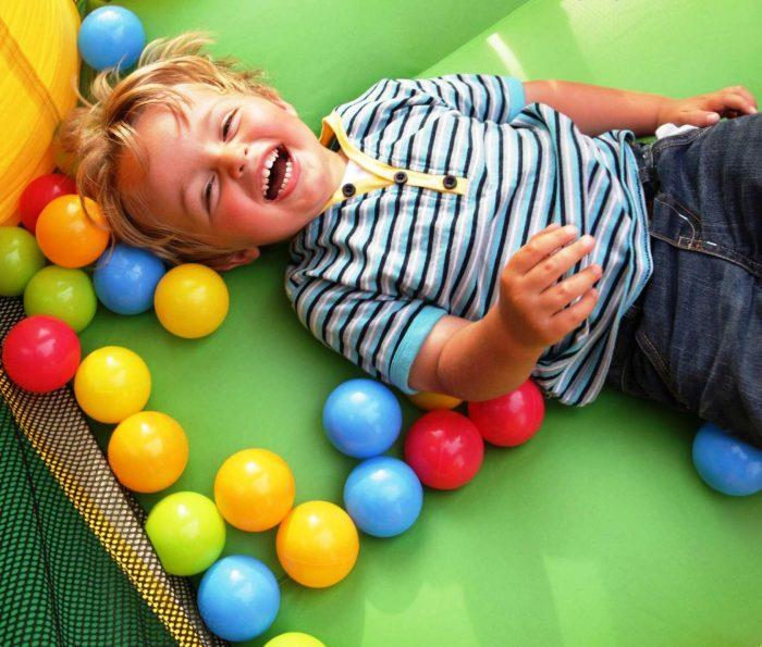 Мальчик лежит в шариках сухого бассейна