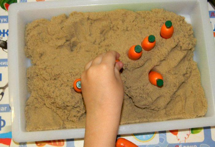 Игрушечная морковь в песке