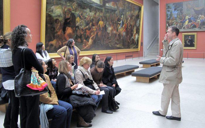 Экскурсовод рассказывает туристам о картинах