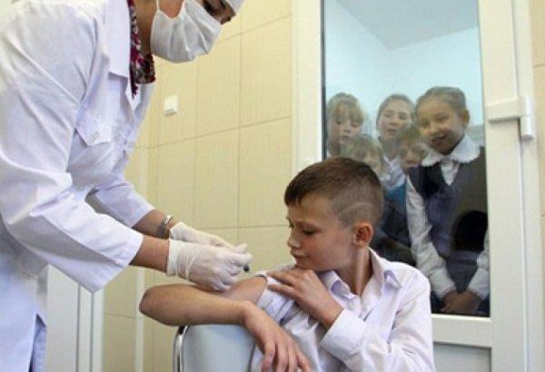 Врач делает школьнику прививку, другие дети наблюдают за этим через стеклянную дверь