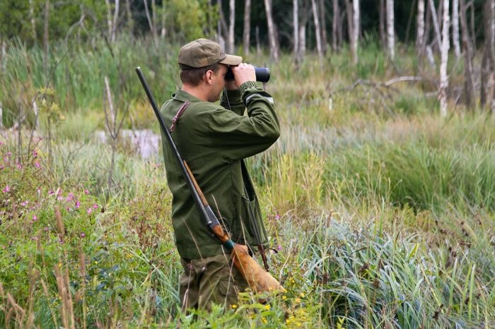 Мужчина в лесу с винтовкой смотрит в бинокль