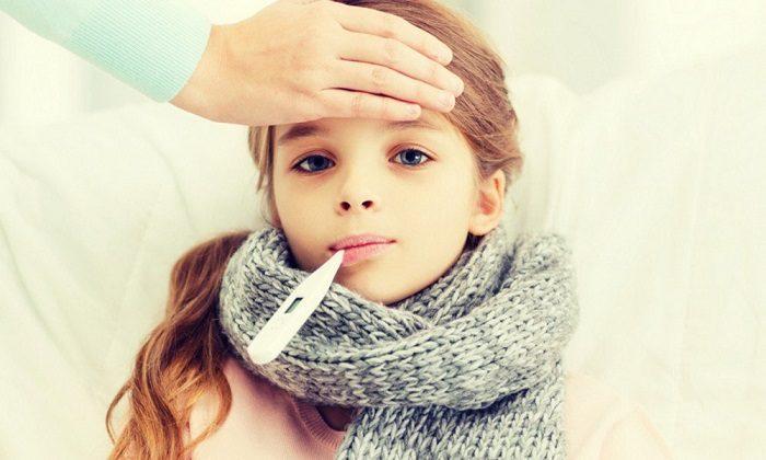 Закутанная шарфом девочка меряет температуру во рту, на лбу у неё женская рука