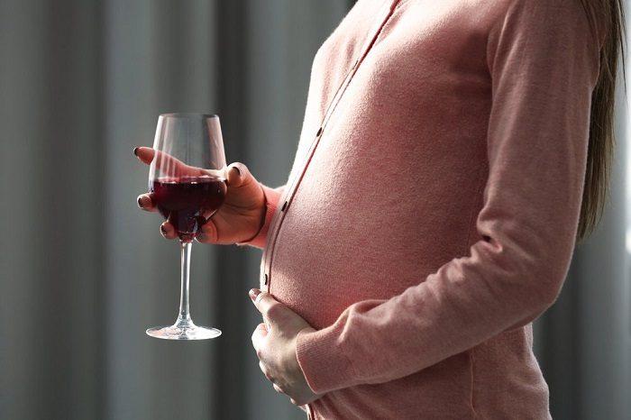 Беременная женщина держит бокал вина