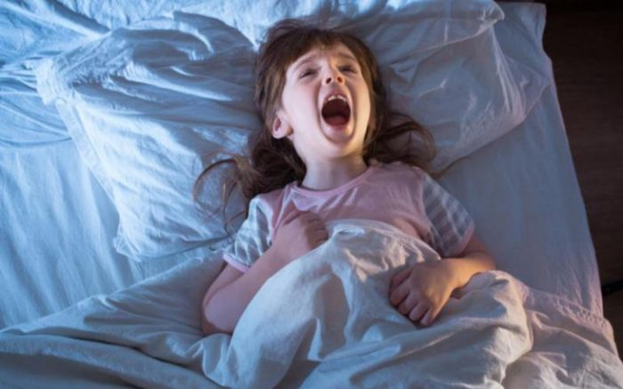Девочка кричит, лёжа в кровати