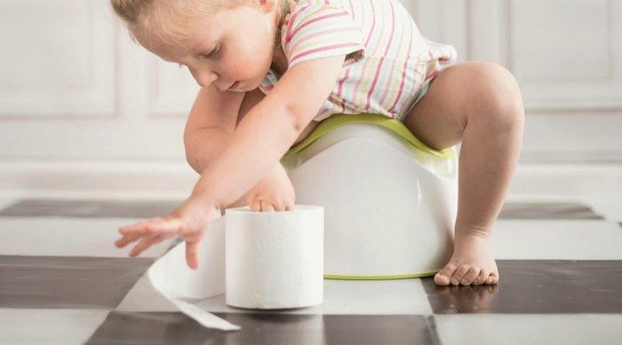 Малыш на горшке разматывает рулон туалетной бумаги