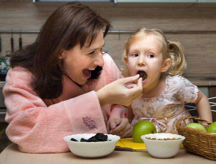 Мама кормит девочку с ложки