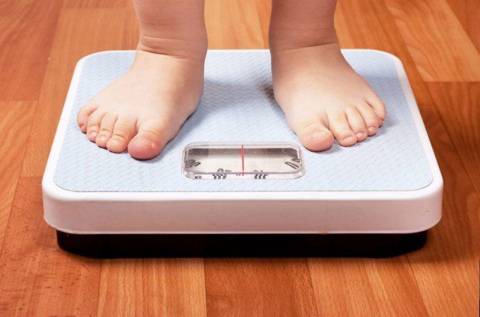 Ребёнок стоит на весах