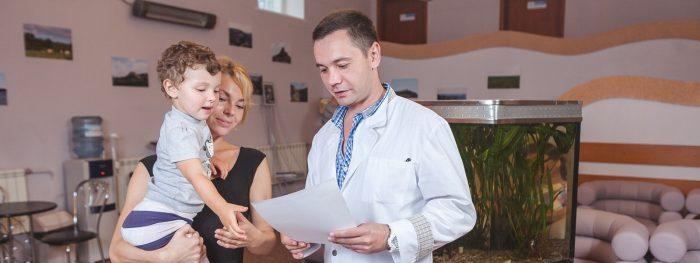 Доктор зачитывает назначение маме с мальчиком