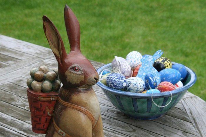 Фигурка зайца с мешком, рядом миска с крашеными родителями