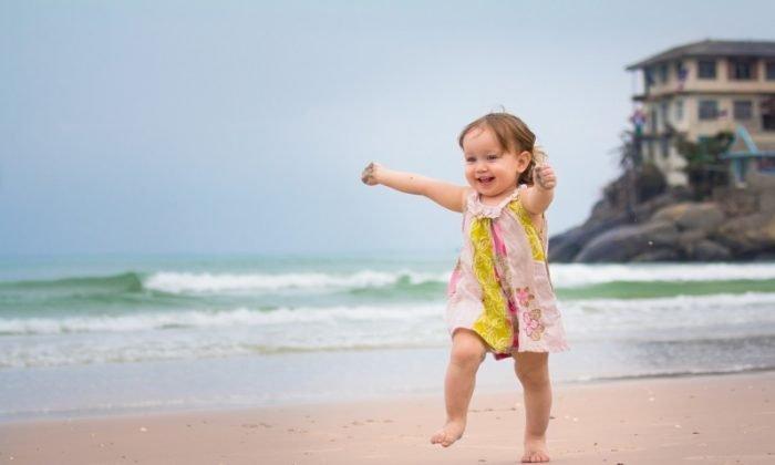 Маленькая девочка бежит по песку рядом с морем