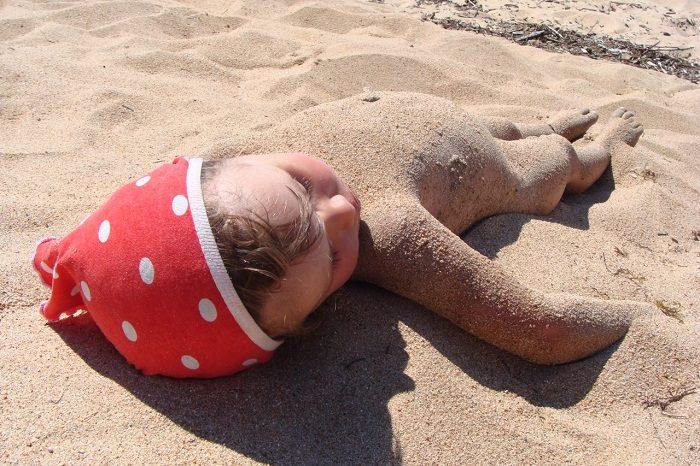 Маленькая девочка лежит на песке, вся покрытая песком