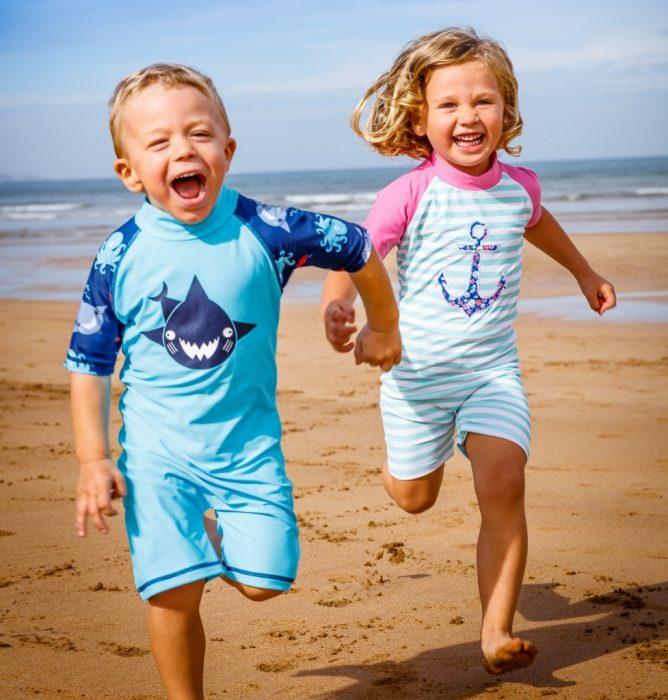 Дети бегут по пляжу в солнцезащитной одежде