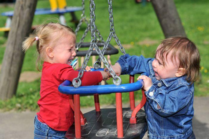 Два маленьких ребенка дерутся на площадке