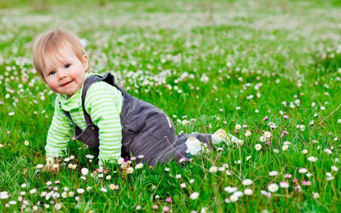 Ребёнок лежит на лужайке с ромашками