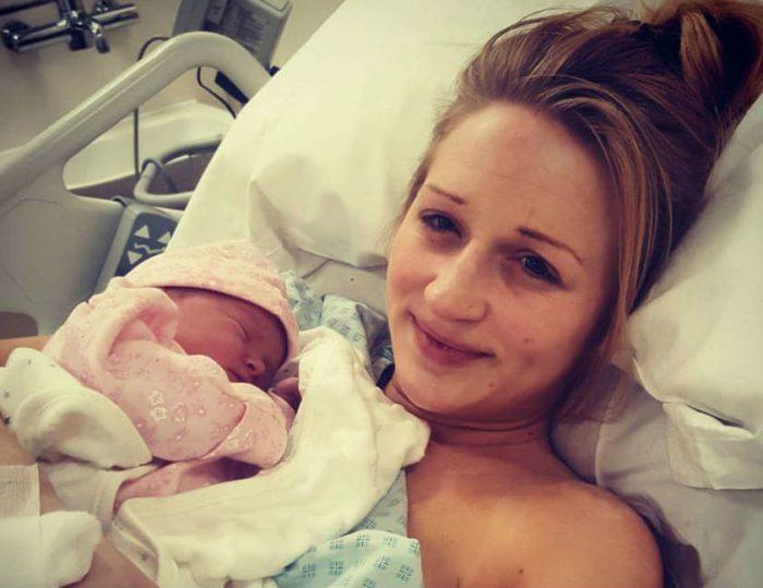 Женщина лежит после родов с младенцем