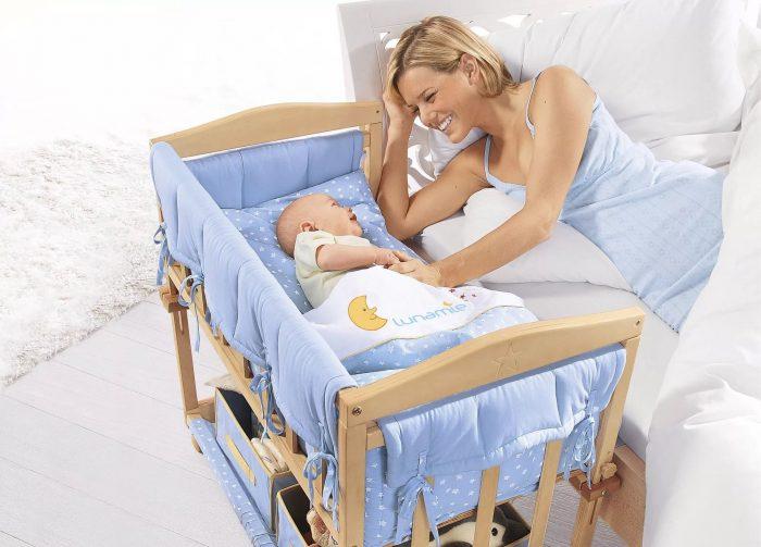 Мама лежит на кровати рядом с малышом в детской кроватке