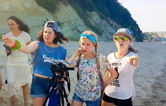 Дети снимают фильм на фоне моря