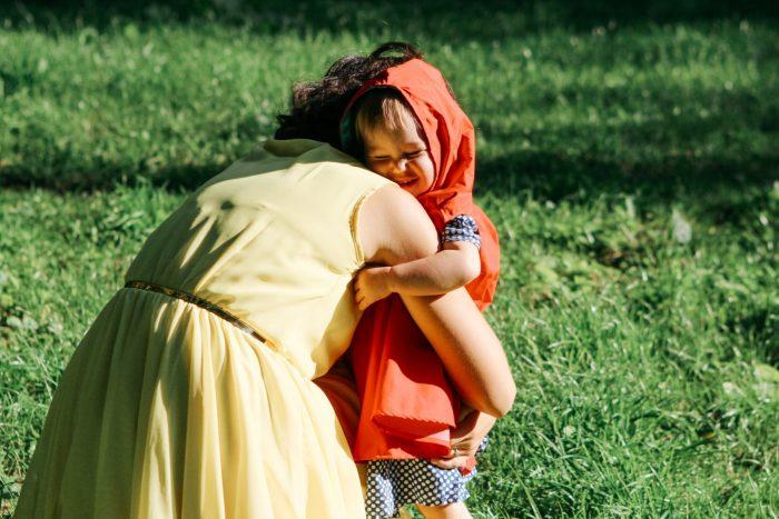 Мама обнимает девочку в оранжевом плаще