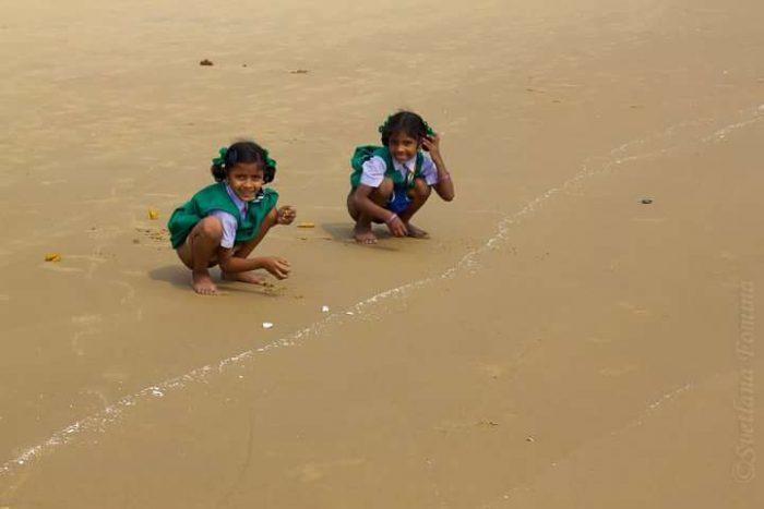 Индийские дети сидят на пляже