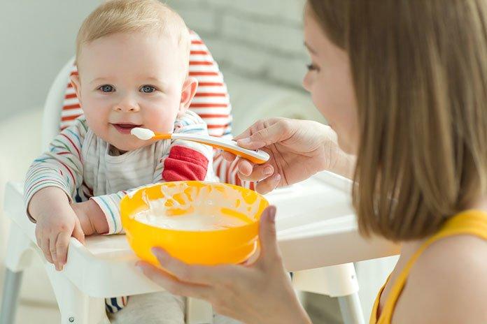 Мама кормит младенца кашей