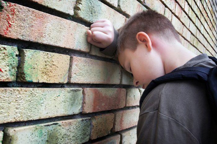 мальчик у кирпичной стены