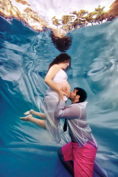 Муж целует живот беременной жены под водой