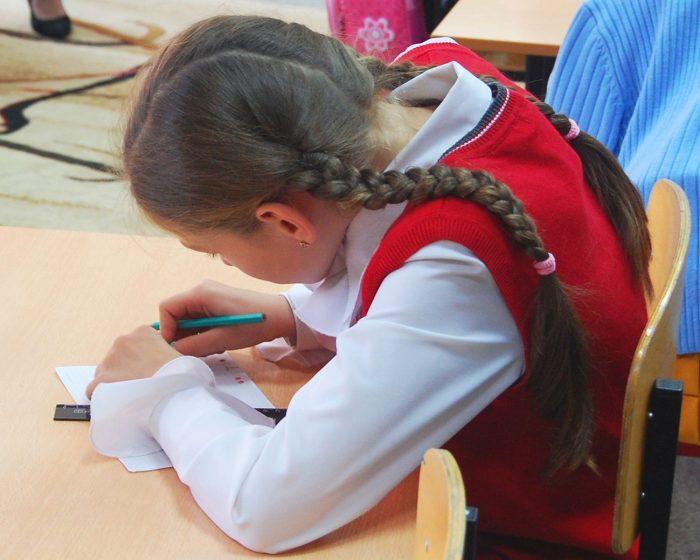Школьница, сгорбившись, сидит за столом