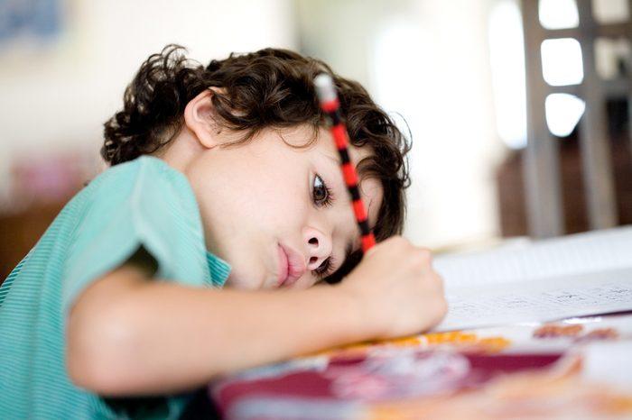 Ребёнок пишет, приблизившись к столу, склонив голову набок