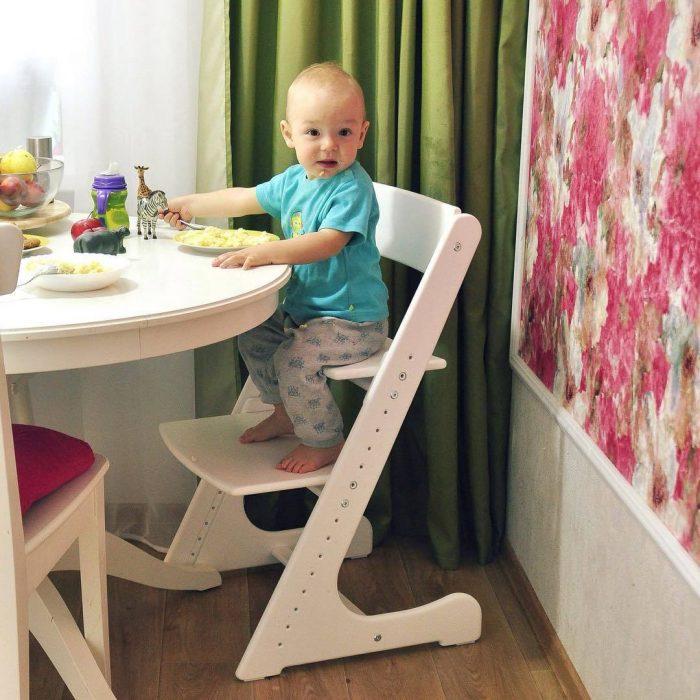 Маленький мальчик ест кашу, сидя за столом на растущем стульчике