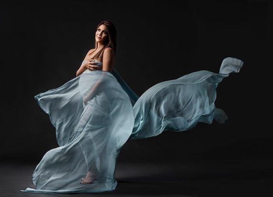 Беременная придерживает руками развевающуюся ткань