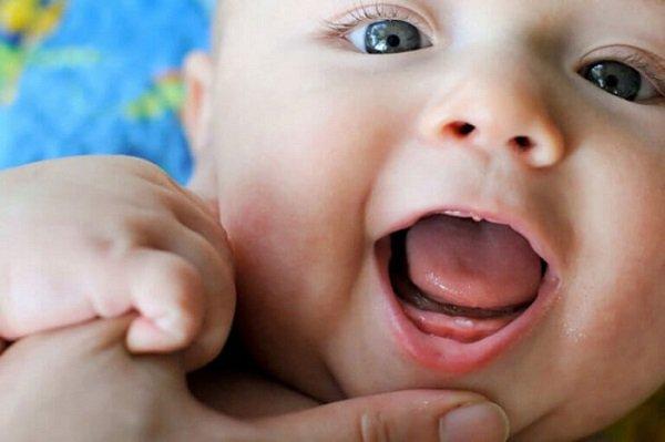 У младенца режется первый зубик