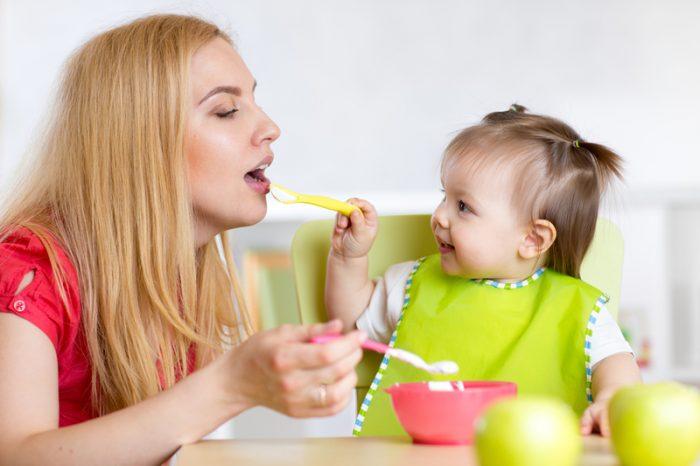 Маленькая девочка кормит маму кашей, а мама в это время также поднимает ложку