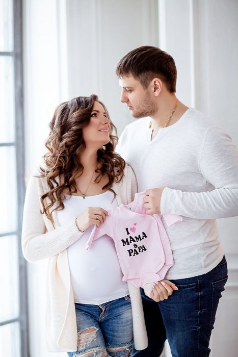 Беременная с мужем держат в руках детский боди