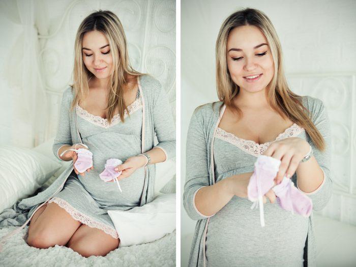 Беременная сидит на кровати и держит в руках пинетки