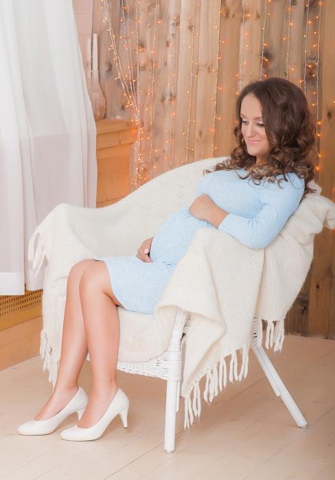 Беременная сидит в кресле