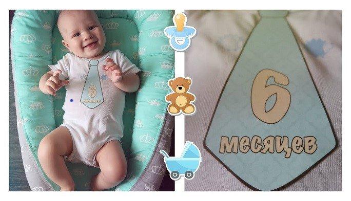Младенец в колыбельке с галстуком с надписью «6 месяцев»