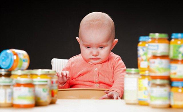 Младенец в окружении баночек с пюре