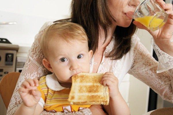Ребёнок кусает блинчик, мама пьёт сок