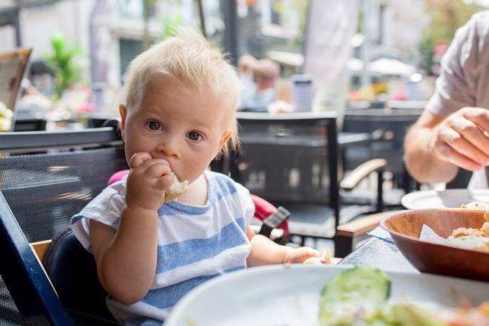 Ребёнок грызёт хлеб, рядом сидит папа