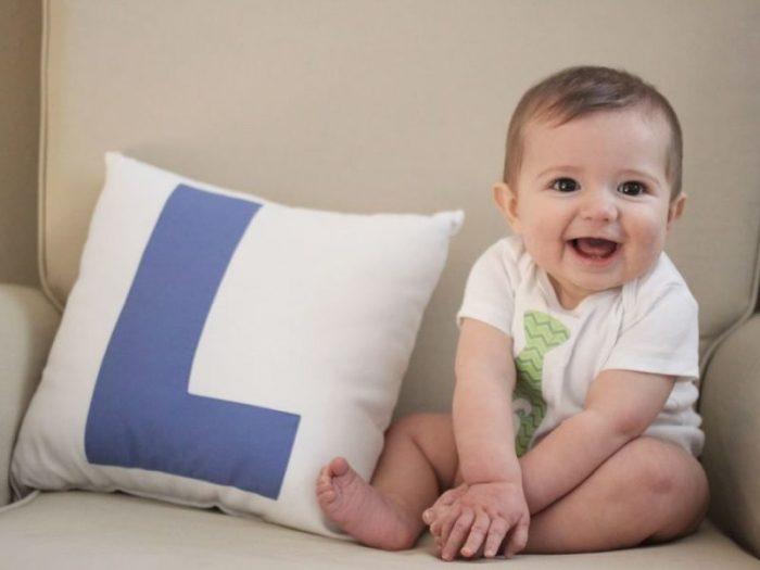Младенец самостоятельно сидит на диванчике