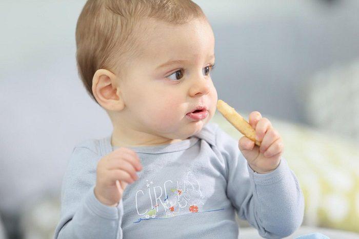 Ребёнок подносит ко рту печенье