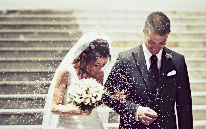 Жених с невестой спускаются по ступенькам, а их обсыпают крупой