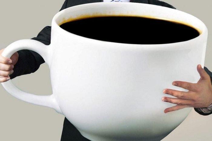 Мужчина держит в руках огромную кружку кофе