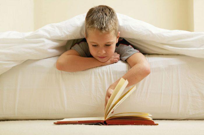 Мальчик читает книгу, лёжа на кровати, книга же лежит на полу