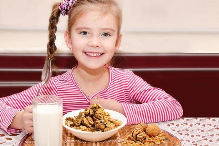 Девочка сидит за столом, перед ней тарелка с гречкими орехами и стакан молока