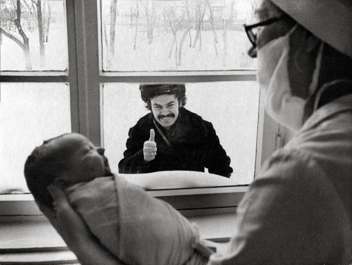 Мужчина заглядывает в окно роддома и смотрит на новорожденного